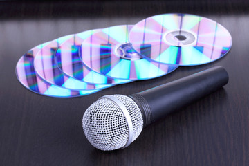 Microphone and cd disks on black table