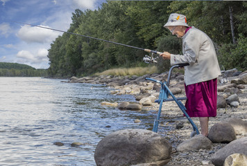 horizontal image of an elderly senior woman with a walker fishing at the edge of the lake with trees and rocks lining the shoreline in the summer time  Wall mural
