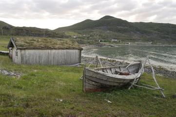 рыбацкая лодка на берегу моря рядом с рыбацкой хижиной