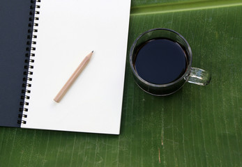 Cup of coffee with books on banana leaf