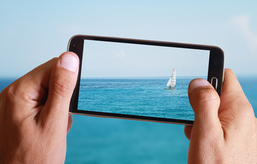 Male hand taking photo of Sailboat, sea, sun, blue, sea, horizon and ocean with cell, mobile phone.