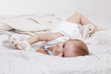 Verspieltes Kleinkind im Bett