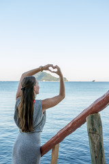 Attractive woman standing at sea on stairs, creating a hart with