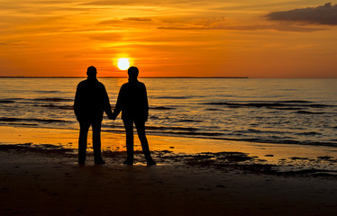 Couple of happy seniors at sandy beach of the Baltic Sea