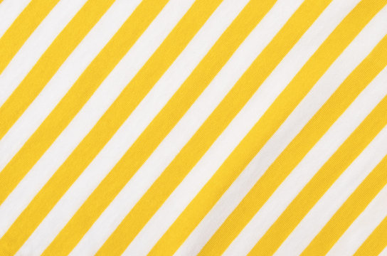 White and yellow striped background. Diagonal stripes pattern on fabric.