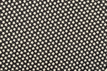 White five-pointed stars on black fabric. Many white stars as a background.