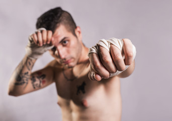 Muai thai fighter posing in studio shot with tattoos