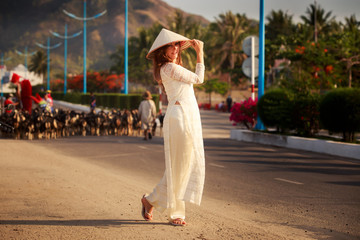 blonde girl in Vietnamese dress stands against defocused flock