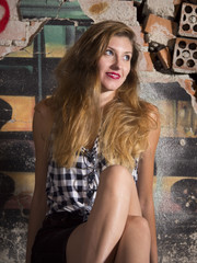 modelo mujer rubia sentada en la calle sonriendo