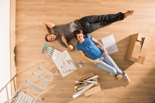 Top view, a modern couple lying on the floor of their new home