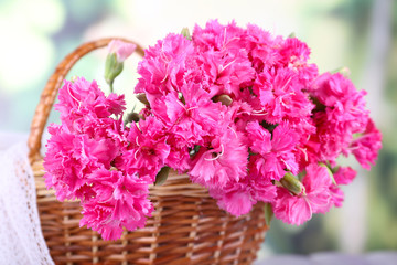 Beautiful bouquet of pink carnation in basket on bright background