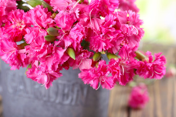 Beautiful bouquet of pink carnation in watering can close up
