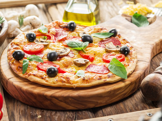 Pizza with mushrooms, salami and tomatoes.