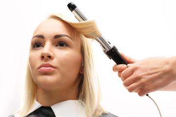 Modelowanie włosów na lokówkę.Kobieta w salonie fryzjerskim, fryzjer kręci włosy na lokówkę.