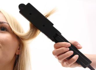 Keratynowe prostowanie włosów.Fryzjer modeluje fryzurę za pomocą prostownicy