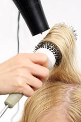 Układanie włosów na szczotkę .Kobieta u fryzjera, fryzjer modeluje włosy na okrągłej szczotce