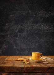 front image of coffee cup over wooden table and autumn leaves in front and blackboard