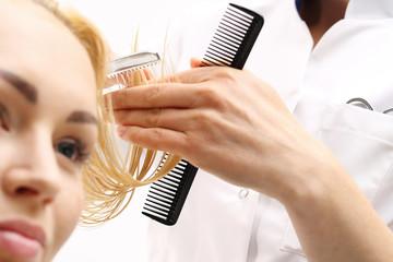 Fryzjer strzyże kobietę nożem chińskim w salonie fryzjerskim