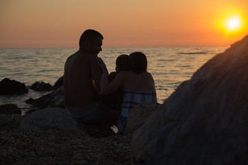 Family at sunset watching the sea
