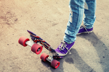 Feet in blue jeans and gumshoes on a skateboard