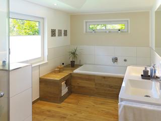 Modernes Badezimmer mit Badewanne, Waschbecken und Holzboden
