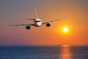 Passenger airplane flying on sunset