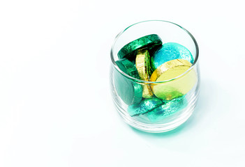 chocolate candy wrapped in colorful foil in each glass on white background