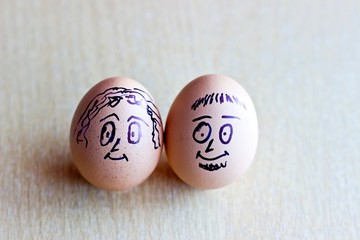Painted easter eggs with man and woman smiling faces. Conceptual image with happy couple