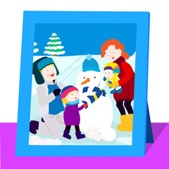 A picture inside a frame. A family making a snowman outside in the winter.