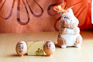 Painted easter eggs with man and woman smiling faces. Eggs on wedding rings near golden gift box. Blurred background with easter bunny. Conceptual funny image. Focus on eggs