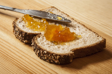 A single slice of whole wheat bread with homemade orange jam on a wooden table.