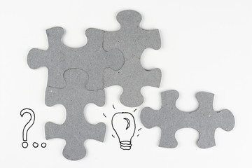 White empty copy space background with puzzle pieces and question mark light lamp