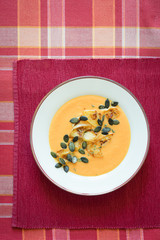 Pumpkin soup served with caramelized apples, pumpkin seeds and thyme