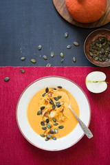 Pumpkin soup with caramelized apples, pumpkin seeds and thyme leaves