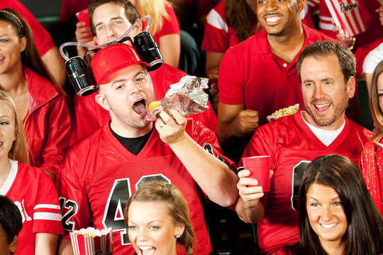 Fans: Male Fan Eats Hot Dog With Beer Helmet On
