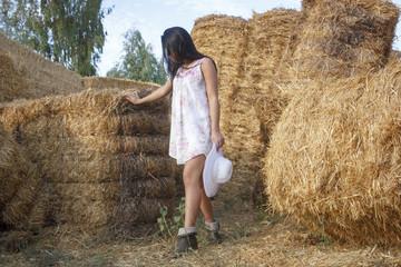Adolescente en las alpacas de heno al final de verano. Chica joven disfrutando en el campo de una tarde de verano. Morena con sombrero en el campo entre la paja.