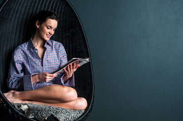 Relaxed woman on bubble chair reading magazine