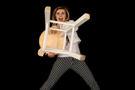 crazy blond woman holding a bar stool out like a lion trainer