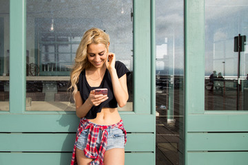 A pretty young California Beach girl reads a text message on her mobile phone. She is outside on a summer day on a boardwalk.