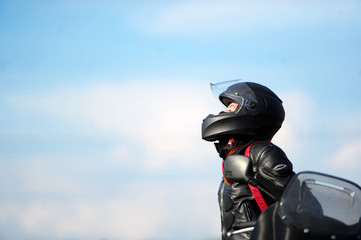 The girl motorcyclist sits on the motorcycle in a helmet