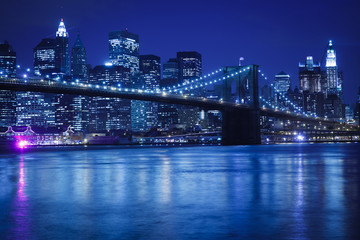 The Brooklyn Bridge against the Manhattan skyline in the early evening.
