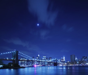The Brooklyn Bridge against the Manhattan skyline and evening moonlit sky.