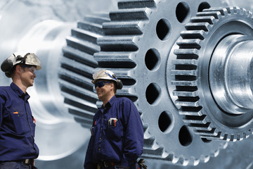 Wall Mural - workers, mechanis with giant gear and cogwheels machinery in background