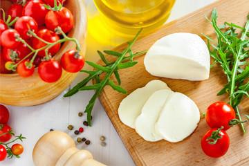 Sliced mozzarella, tomatoes and arugula on table