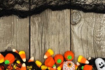 Halloween candy and spooky black cloth double border against a rustic wood background