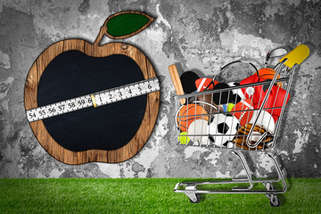 shopping cart with sporting goods on grass in front of stone wall with apple shaped blackboard