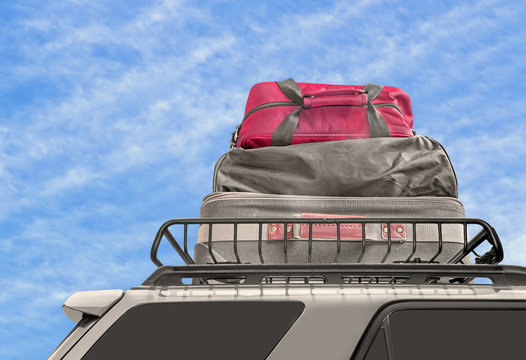 Luggage on van roof rack, blue sky and cloud background, copyspace