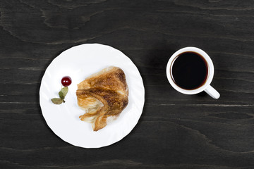Cup of tea with puff pastry on a black wooden surface