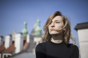 Beautiful woman with a serious expression on her face looking straight ahead with a view of old town in the background