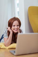 lächelnde frau liegt auf dem fußboden und schaut auf laptop